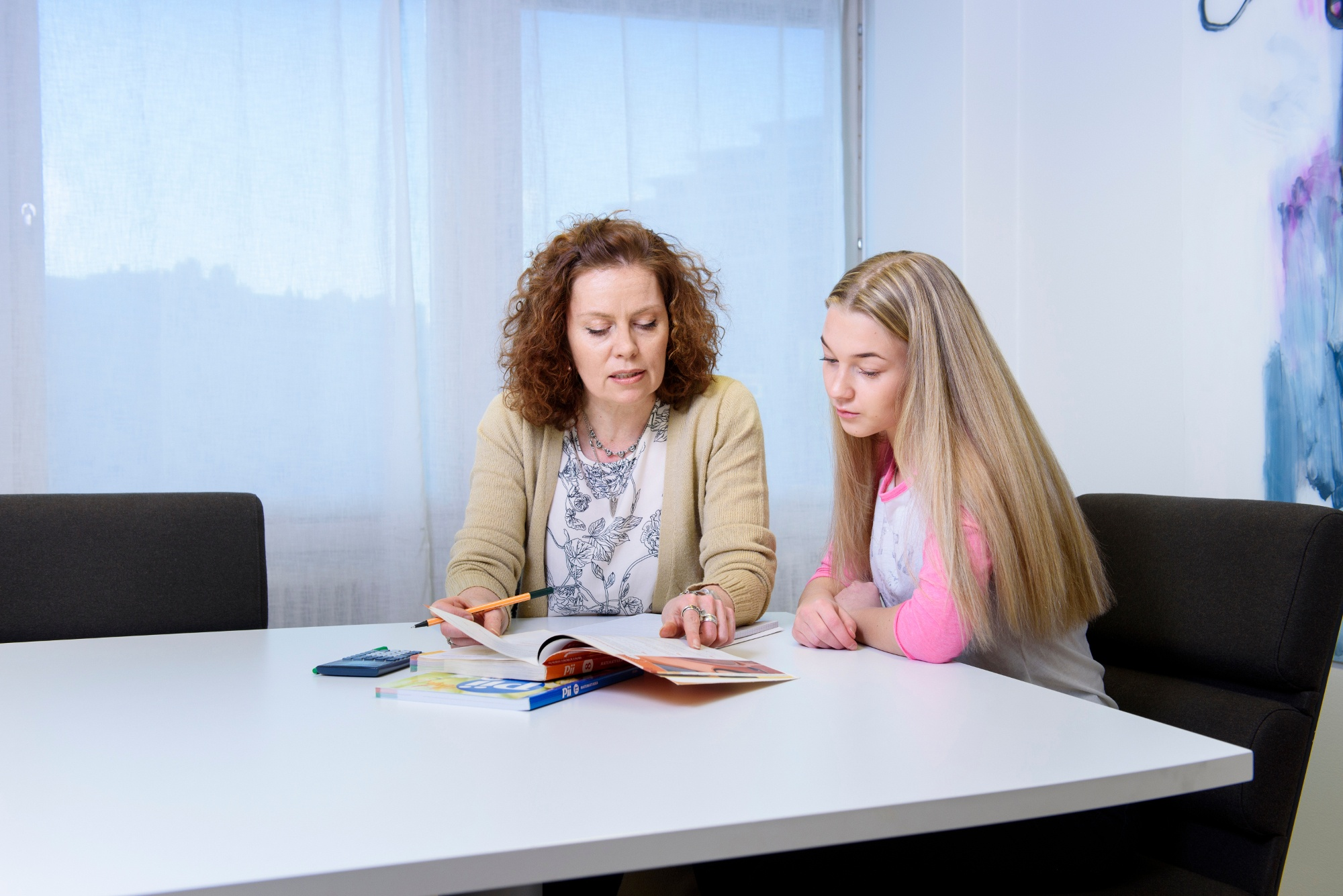 A female teacher teaching a teenage girl in a private tutoring session.