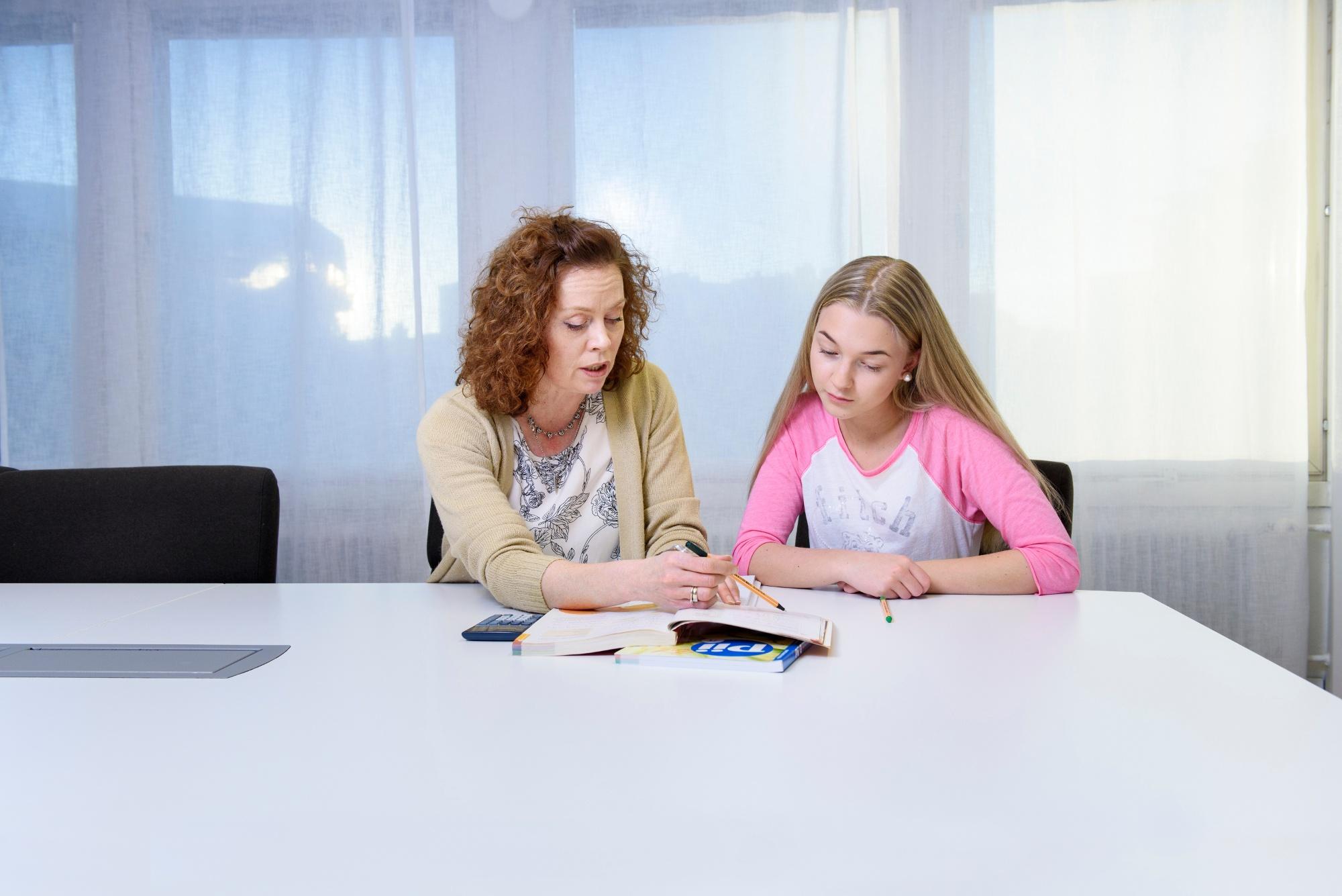 Maths teacher teaching a teenage girl.