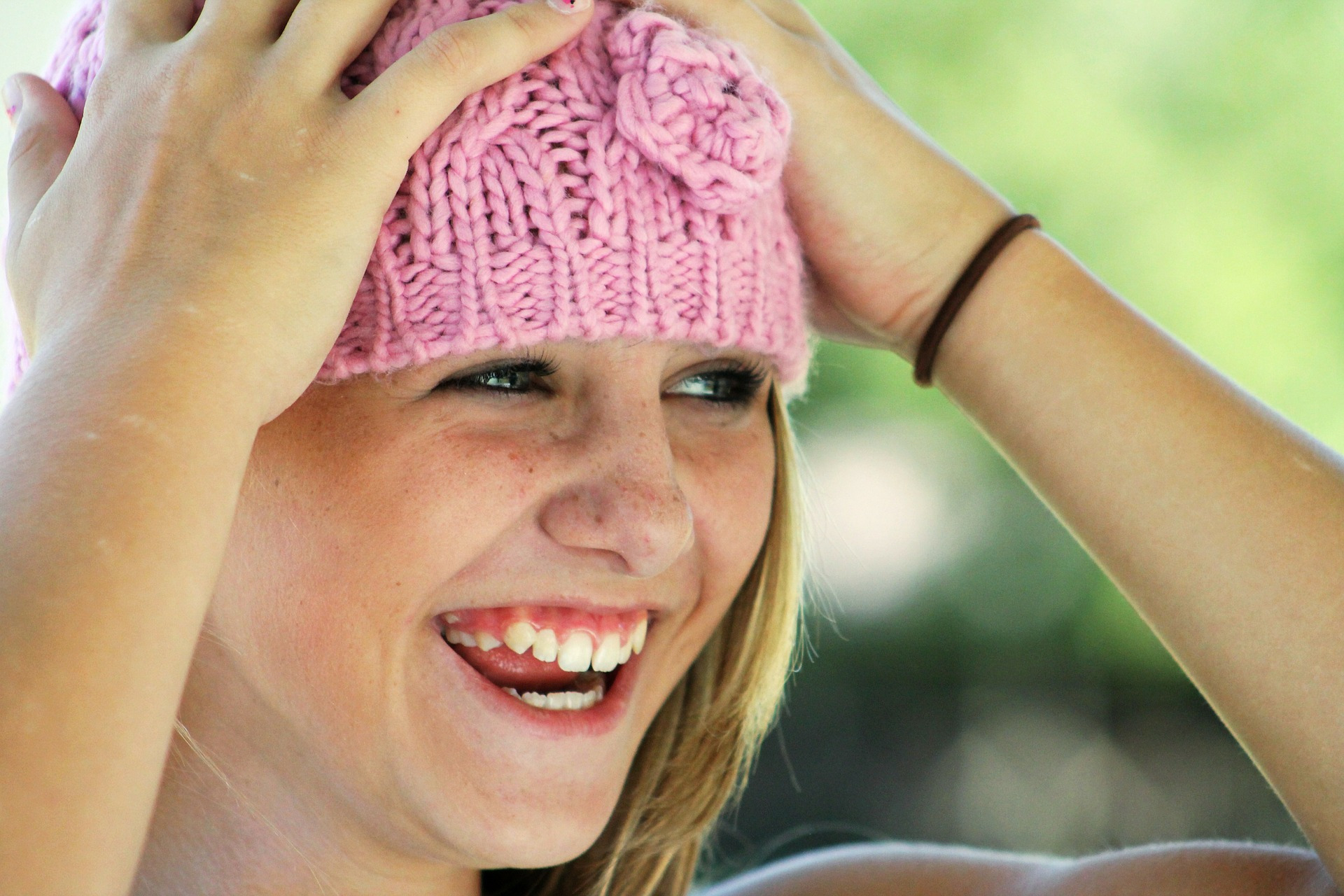 A girl with a pink woolly hat on her head.
