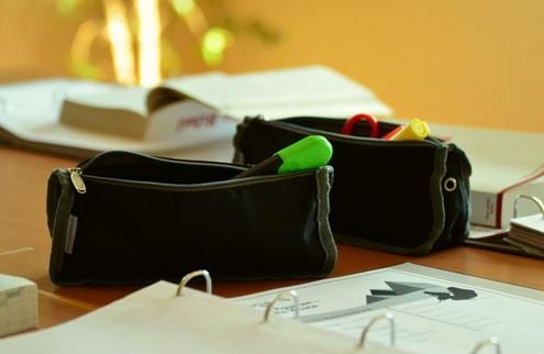 Two black pencil cases on a table with marker pens showing.