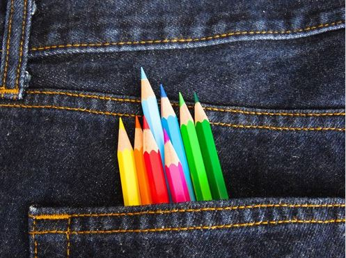 Coloured pencil crayons in a pocket of blue jeans.